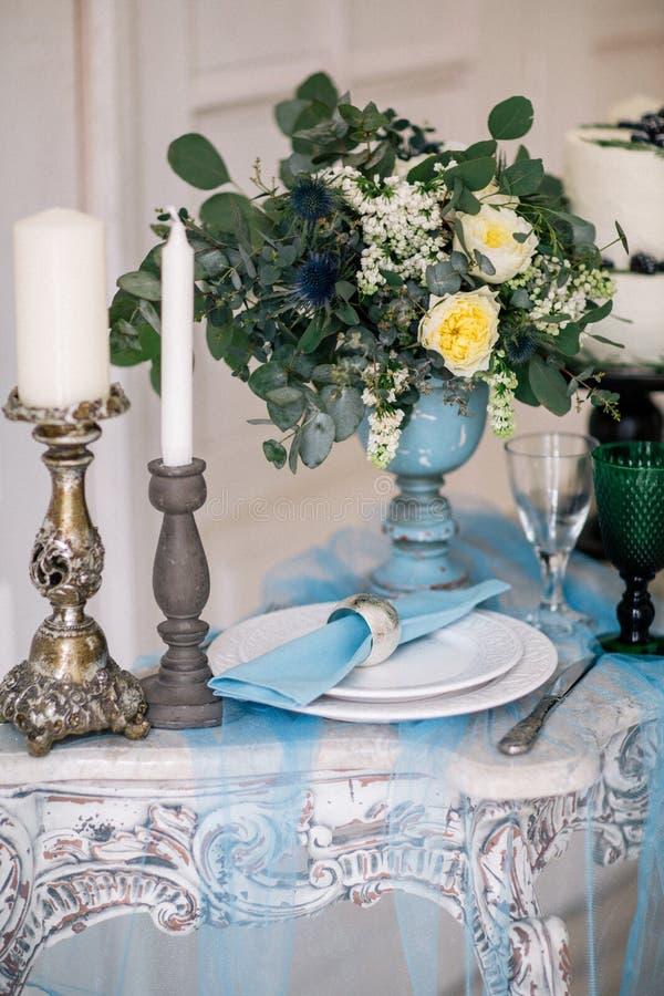 Красивый украсьте таблицу с свечами, вазой с цветками и свадебным пирогом на таблице в студии стоковое фото