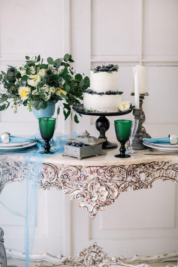 Красивый украсьте таблицу с свечами, вазой с цветками и свадебным пирогом на таблице в студии стоковые изображения rf