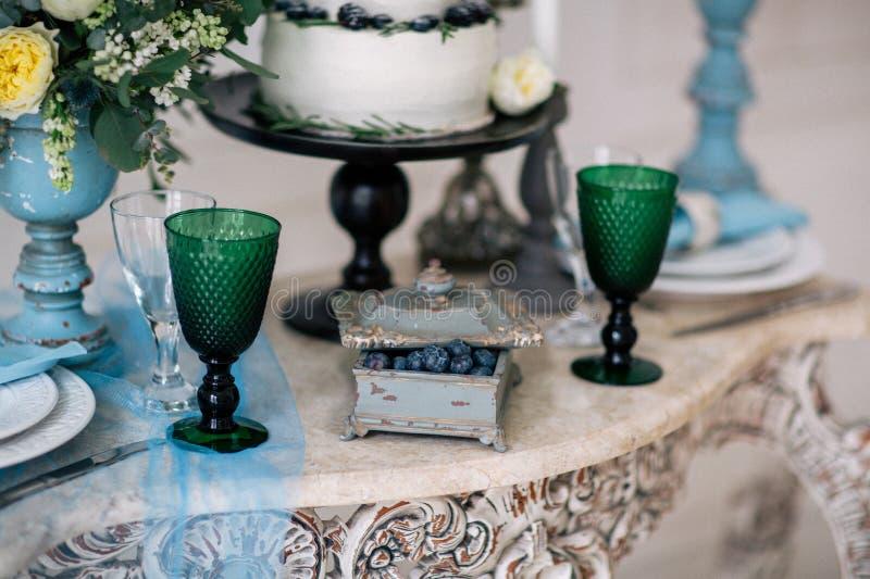 Красивый украсьте таблицу с свечами, вазой с цветками и свадебным пирогом на таблице в студии стоковое фото rf