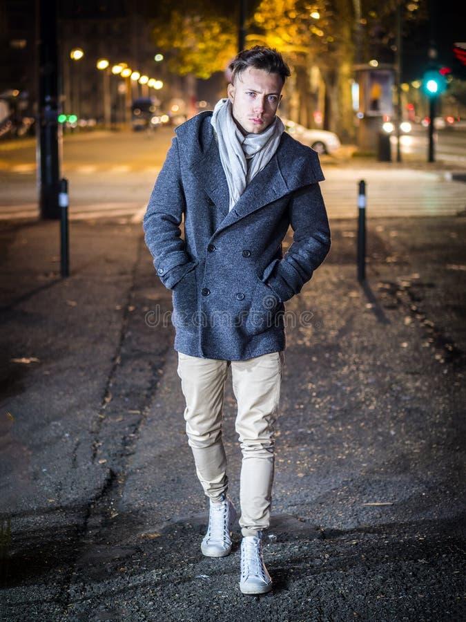 Красивый ультрамодный молодой человек, стоя на тротуаре вечером стоковое фото