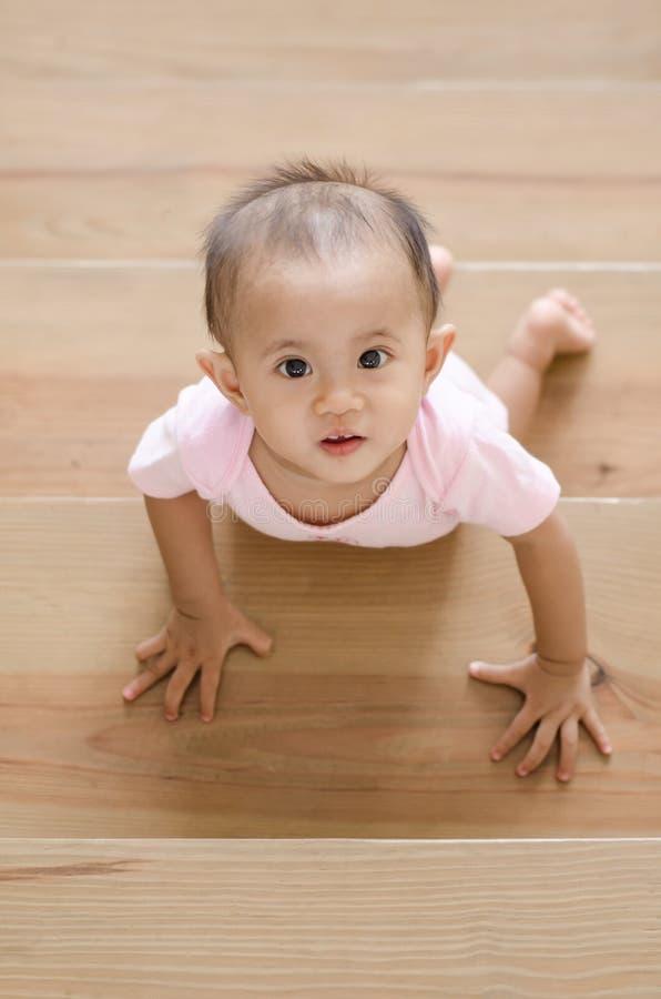 Красивый усмехаясь азиатский ребёнок пока вползающ вверх по лестнице стоковые изображения