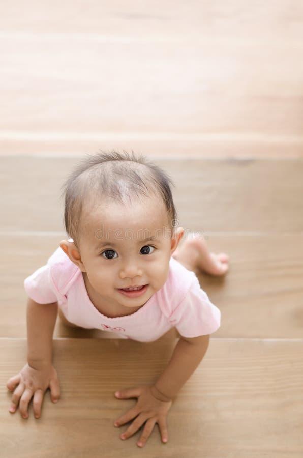 Красивый усмехаясь азиатский ребёнок пока вползающ вверх по лестнице стоковое фото