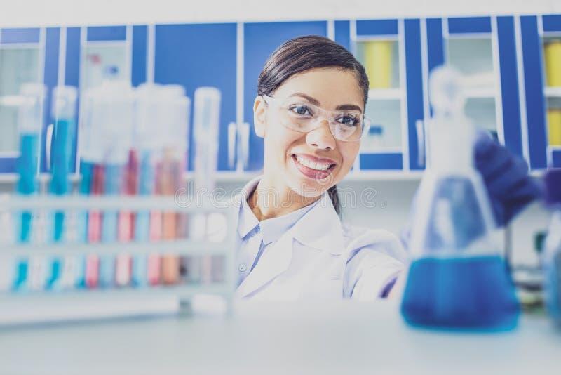 Красивый усмехаясь врач стоя близко пробирки стоковые фото