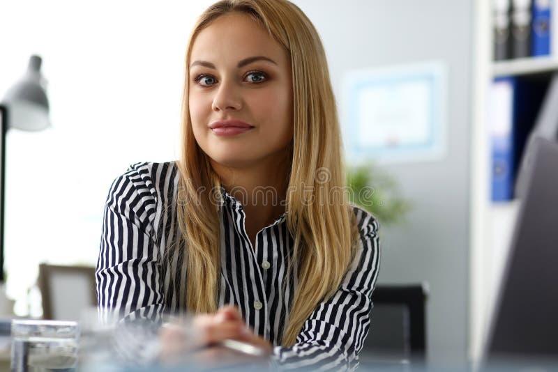 Красивый усмехаясь женский CEO (главный исполнительный директор) на worktable смотря в камере стоковые фотографии rf