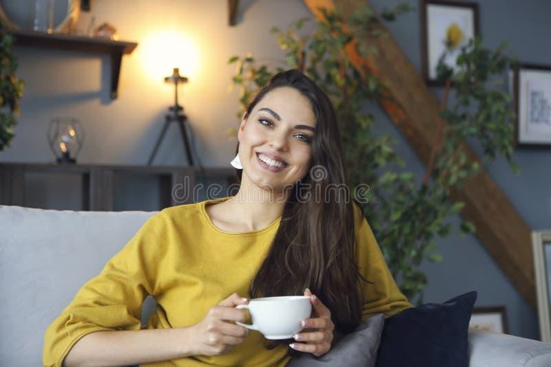 Красивый усмехаясь кофе женщины брюнета выпивая стоковое изображение