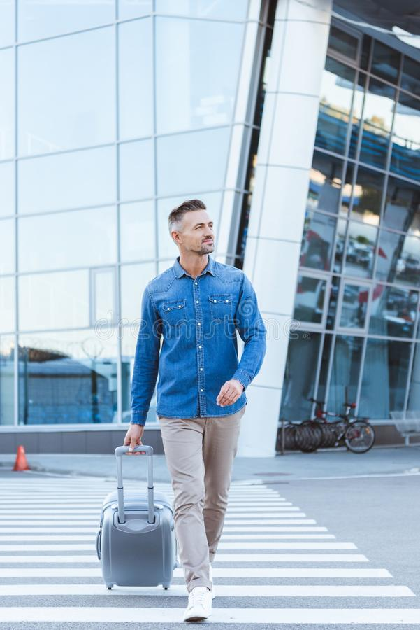 Красивый усмехаясь пешеход скрещивания человека, вытягивая его багаж и стоковое изображение