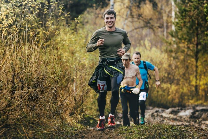Красивый усмехаясь человек бежать в лесе осени стоковые изображения