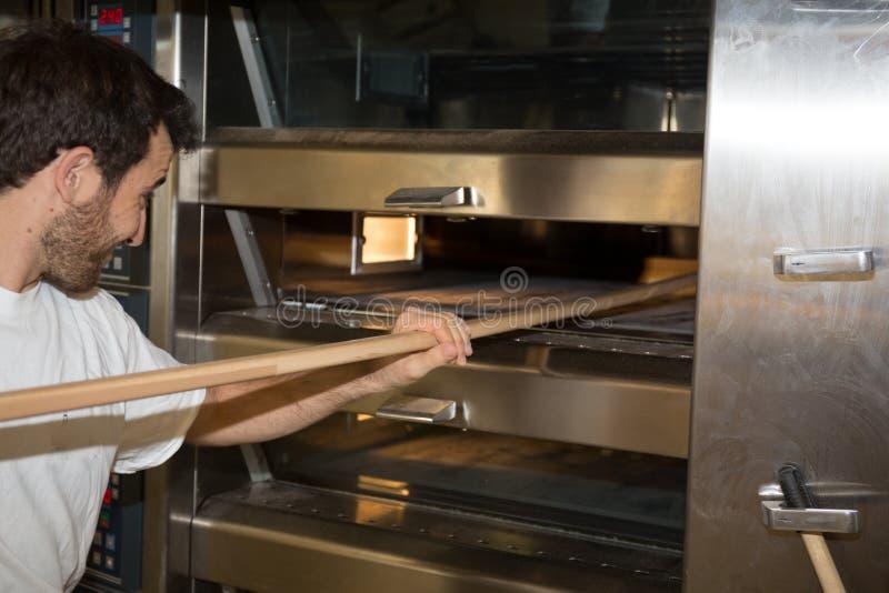 Красивый хлебопек принимая вне с лопаткоулавливателем свеже испек хлеб от печи стоковые фотографии rf