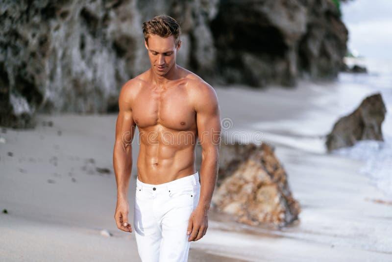 Красивый человек без рубашки и в белых брюках идя вперед на песчаный пляж Гай с сексуальным телом фитнеса стоковое фото rf