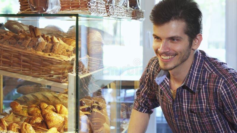 Красивый человек выбирая десерты от витрины на хлебопекарне стоковое изображение rf