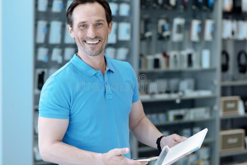 Красивый человек выбирая новое устройство для себя стоковое фото