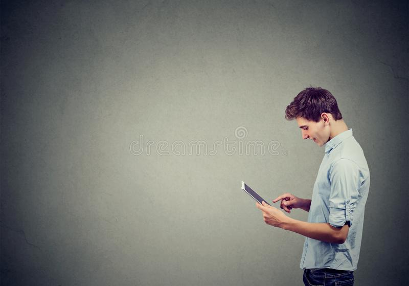 Красивый человек в голубой рубашке использует цифровые таблетку и усмехаться стоковая фотография