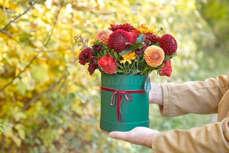 Красивый человек в костюме держа коробку рук праздничную зеленую с чувствительными цветками Подарок ко дню женщин Закройте вверх  стоковое фото rf