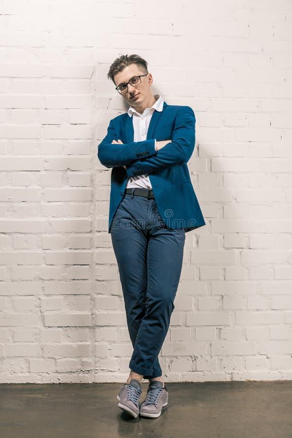 Красивый человек в представлять синего пиджака и зрелищ внешний белой кирпичной стеной Красота ` s людей, мода женщина типа пер д стоковая фотография rf