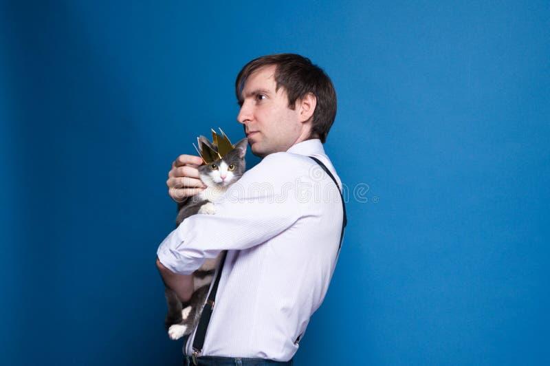красивый человек в розовой рубашке и черных подтяжках смотря в расстояние, держа и штрихуя серого кота в золотой кроне на голубой стоковая фотография rf