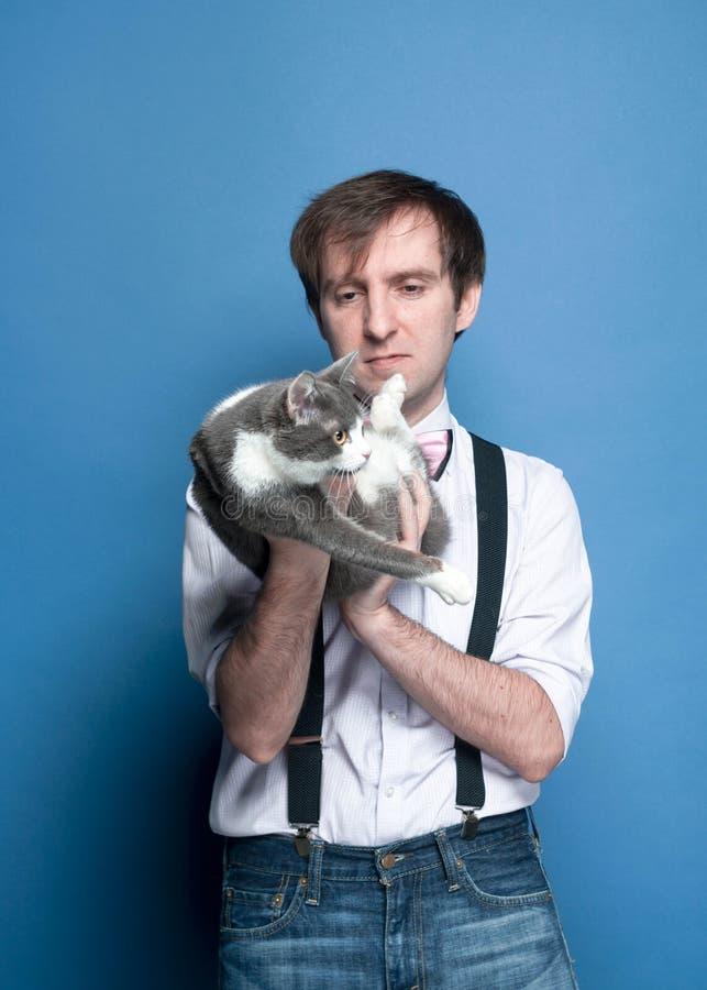 Красивый человек в рубашке держа и смотря милого серого и белого кота стоковая фотография rf