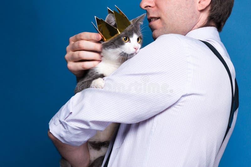 Красивый человек в рубашке и подтяжках держа и штрихуя милого серого кота в золотой кроне стоковые изображения