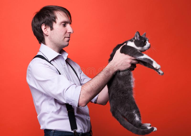 Красивый человек в рубашке со свернутыми рукавами держа милого серого и белого кота и смотря его назад стоковые фотографии rf