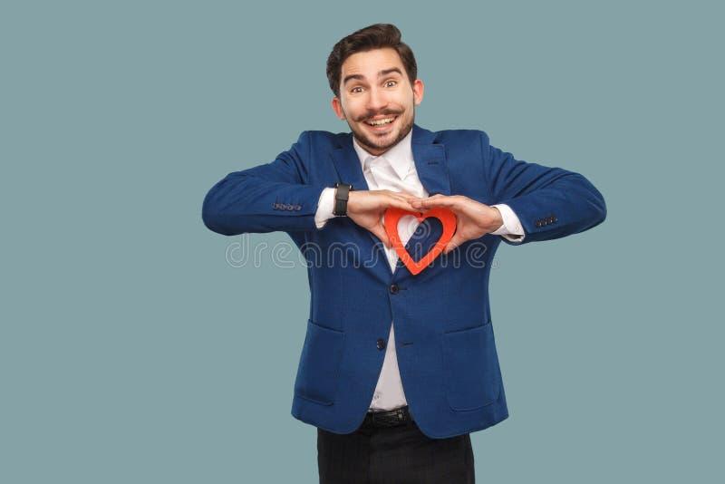Красивый человек в синем пиджаке и белой рубашке, положении и holdin стоковая фотография