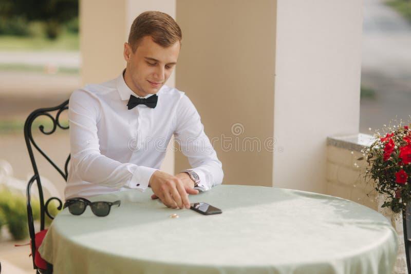 Красивый человек в телефоне пользы рубашки и бабочки человек светлых волос снаружи Sist человека таблицей и попробовать дальше со стоковые фото