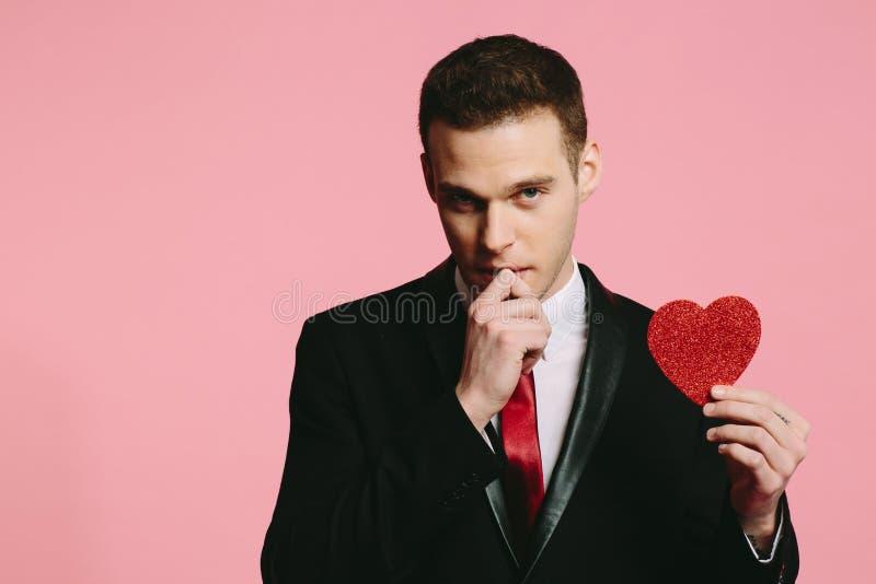 Красивый человек в черном костюме держа красное сердце на день ` s валентинки стоковая фотография