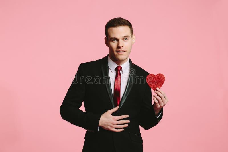 Красивый человек в черном костюме держа красное сердце на день ` s валентинки стоковое фото rf