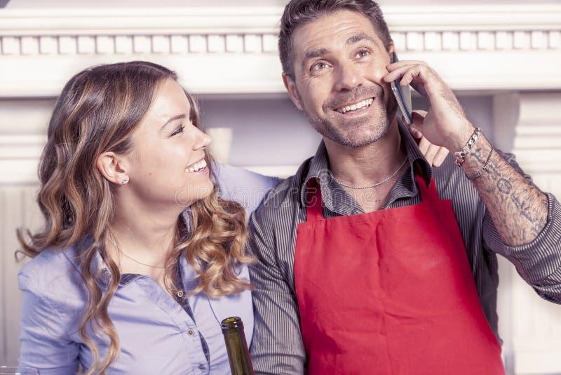 Красивый человек говоря на умном телефоне в кухне стоковые фотографии rf