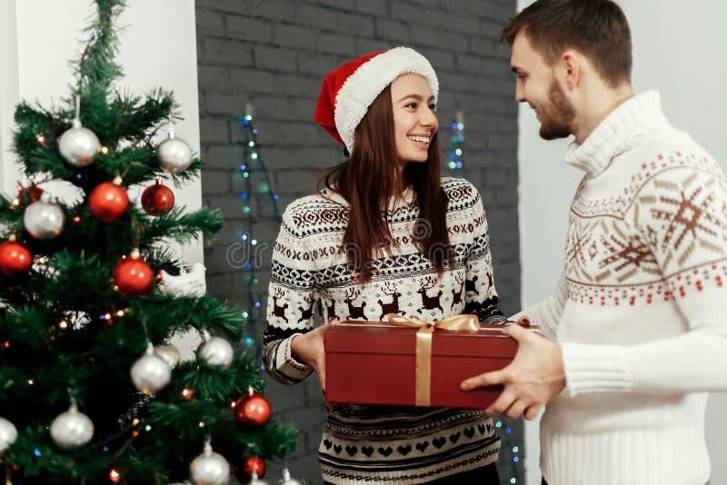 Красивый человек давая подарок на рождество к его красивой женщине внутри стоковая фотография