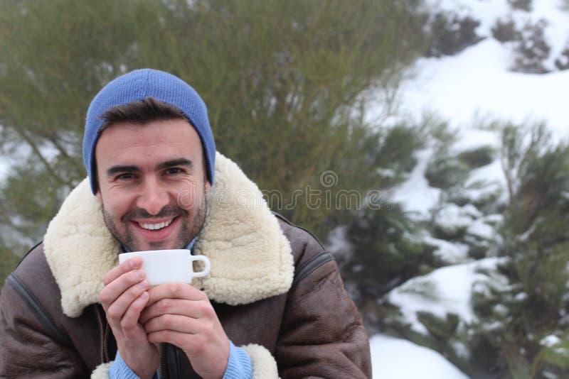 Красивый человек держа теплую чашку кофе в зиме стоковая фотография rf
