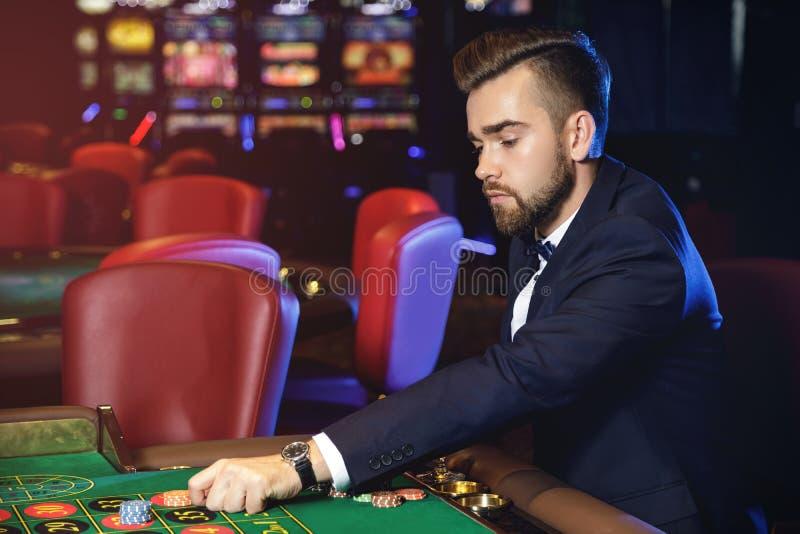 Красивый человек играя рулетку в казино стоковая фотография rf