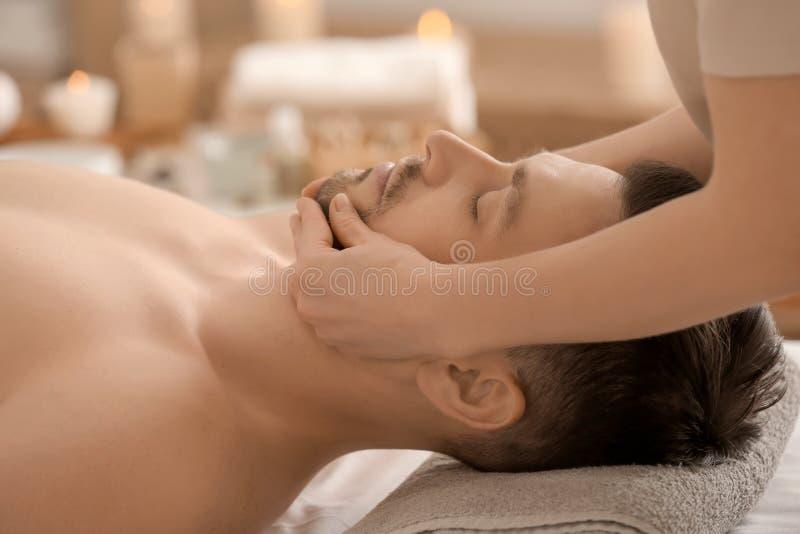 Красивый человек имея лицевой массаж в салоне спа стоковое фото rf