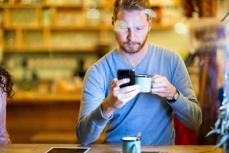 Красивый человек используя мобильный телефон в кофейне стоковые изображения rf