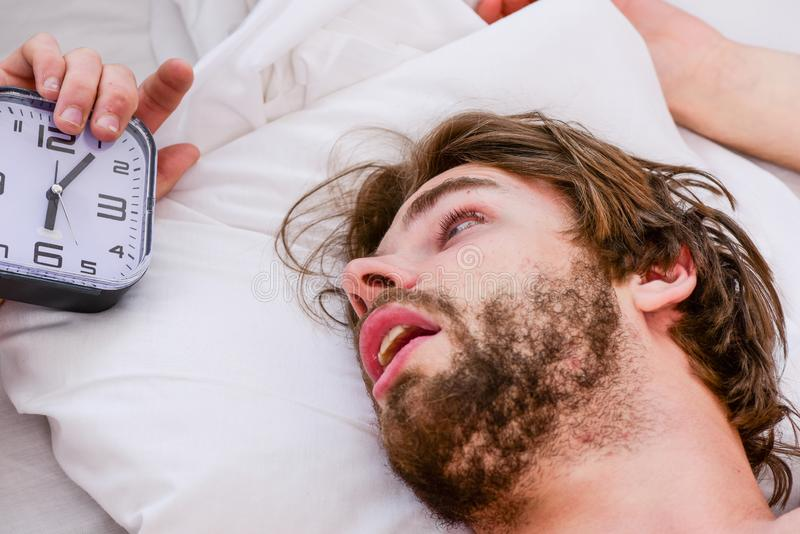 Красивый человек используя часы в кровати после просыпать вверх в утре Просыпать ленивого человека счастливый вверх в руках крова стоковые изображения