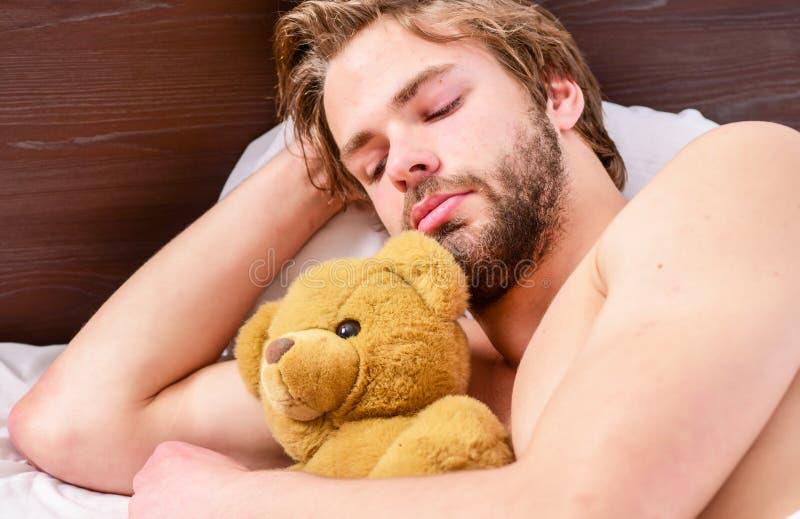 Красивый человек используя часы в кровати после просыпать вверх в утре Просыпать ленивого человека счастливый вверх в руках крова стоковое изображение rf