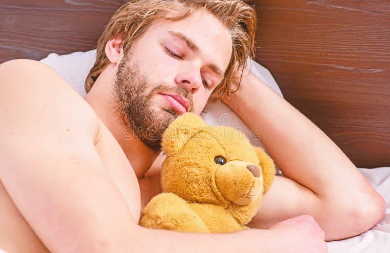 Красивый человек используя часы в кровати после просыпать вверх в утре Просыпать ленивого человека счастливый вверх в руках крова стоковые фото