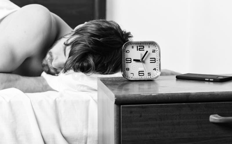 Красивый человек используя часы в кровати после просыпать вверх в утре Просыпать ленивого человека счастливый вверх в руках крова стоковое фото rf
