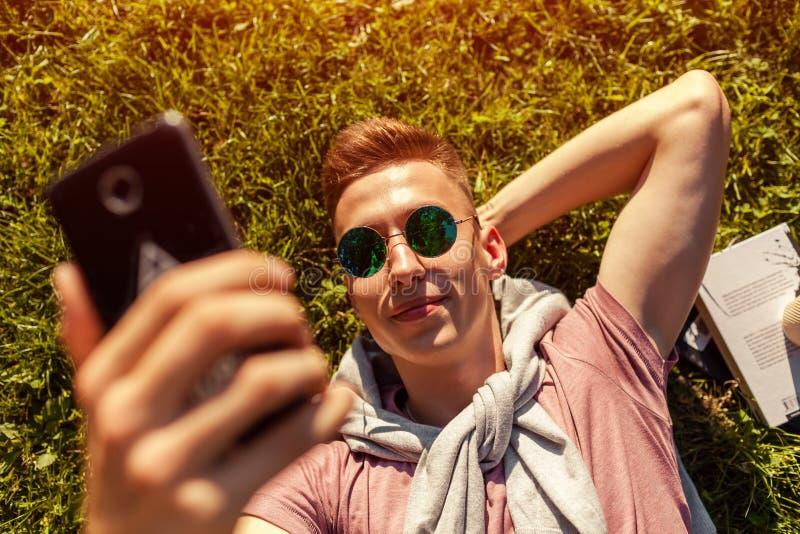 Красивый человек коллежа охлаждая весной парк кампуса Счастливый студент парня лежа на selfie травы и взятий стоковые фото