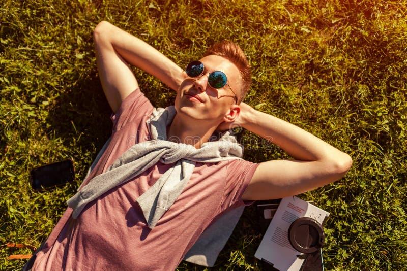 Красивый человек коллежа охлаждая весной парк кампуса Счастливый студент парня лежа на траве с его телефоном и кофе рядом с стоковая фотография