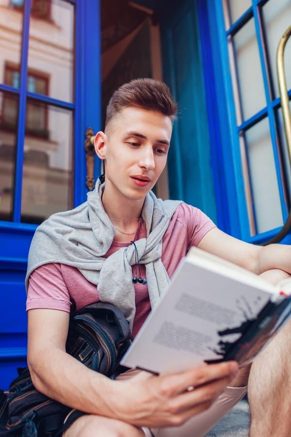 Красивый человек коллежа читая книгу сидя кафем Счастливый студент парня с рюкзаком уча outdoors Образование стоковое фото