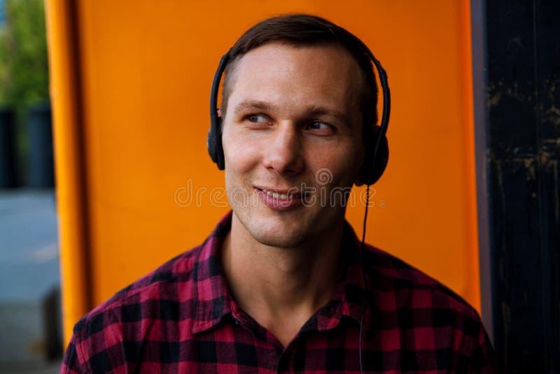 Красивый человек наслаждаясь музыкой через наушники стоковое фото
