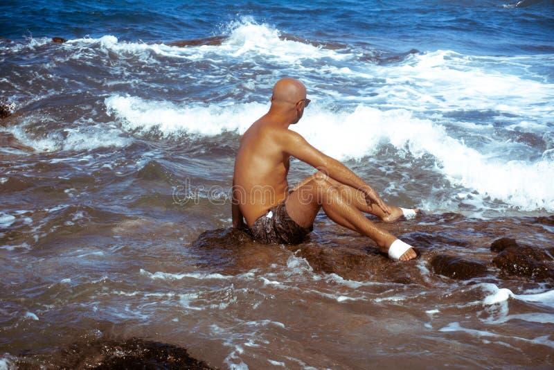 Красивый человек на морском скалистом береге стоковая фотография
