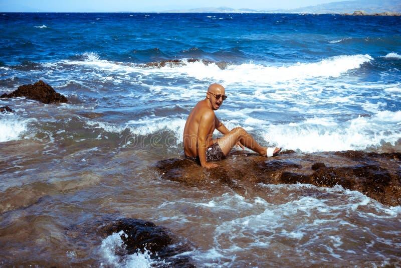 Красивый человек на морском скалистом береге стоковое изображение rf