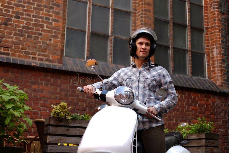 Красивый человек нося вскользь одежды в шлеме, ехать на ретро классическом самокате, вдоль старых улиц в Европе стоковое фото