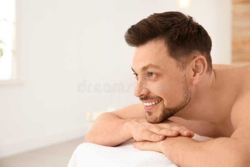 Красивый человек ослабляя на таблице массажа в салоне спа стоковые изображения