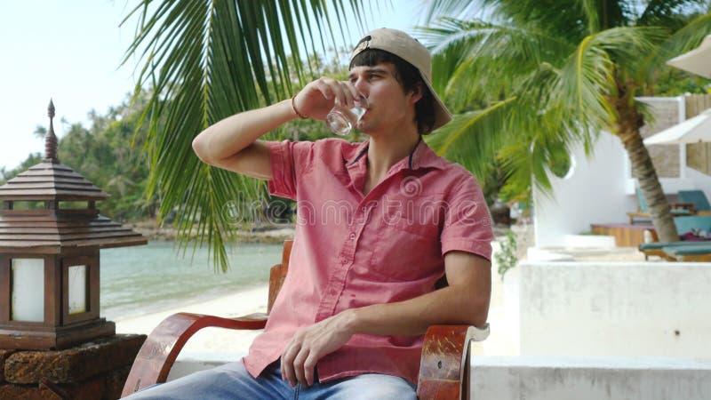 Красивый человек питьевая вода в кафе на пляже стоковая фотография