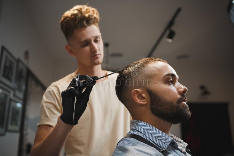 Красивый человек получает стрижку парикмахером на предпосылке парикмахерскаи Привлекательный парень в салоне красоты стоковая фотография
