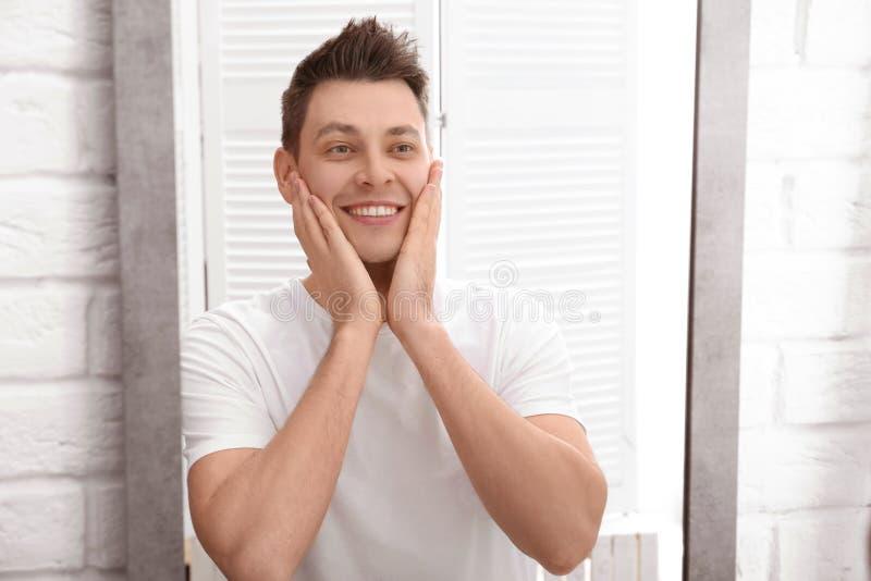 Красивый человек после брить около зеркала стоковое изображение rf