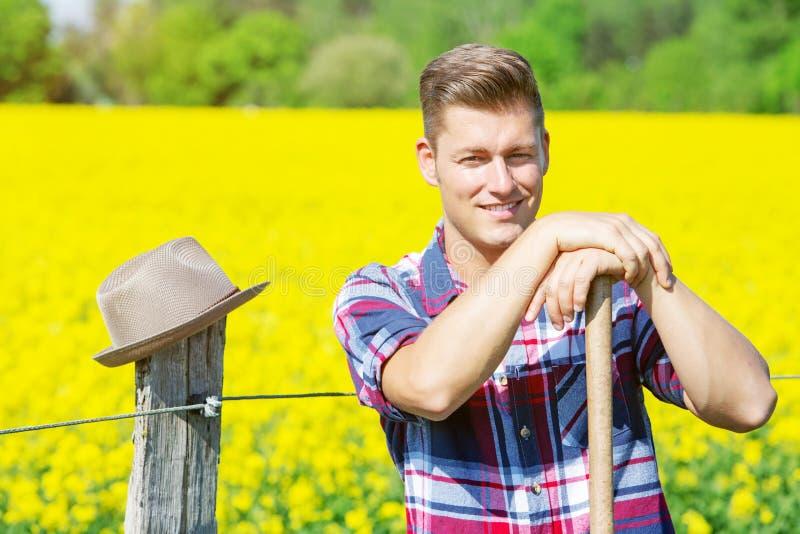 Красивый человек при вила стоя перед желтым полем стоковое изображение