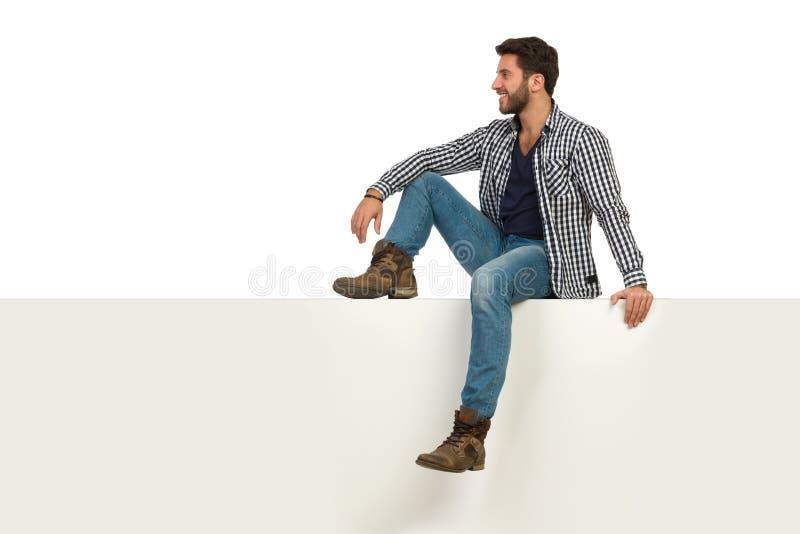 Красивый человек сидеть расслабленный на верхней части и смотреть прочь стоковое изображение rf