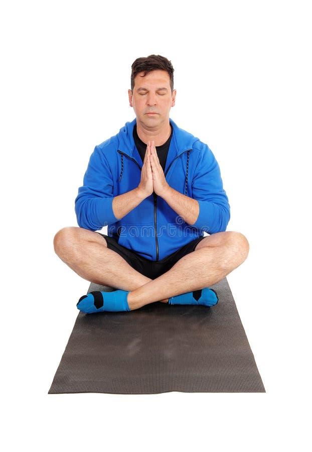 Красивый человек сидя на поле делая йогу стоковые изображения rf
